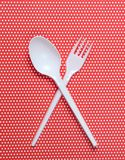Plastic spoon and fork on red tablecloth in polka dots. top view. Plastic spoon and fork on red tablecloth in polka dots. top view stock image