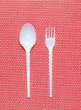 Plastic spoon and fork on red tablecloth in polka dots. top view. Plastic spoon and fork on red tablecloth in polka dots. top view stock photo