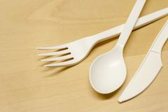 Plastic spoon and fork on a wooden table royalty free stock image