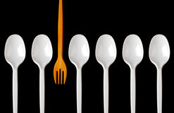 Plastic spoons and fork. A row of plastic spoons and one yellow fork. Isolated on white Stock Photos