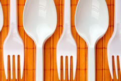 Plastic spoons and forks. A row of plastic silverware. Spoons and forks Stock Images