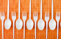 Plastic spoons and forks. A row of plastic silverware. Spoons and forks Stock Photo