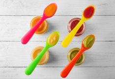 Plastic spoons and jars with baby food Stock Images