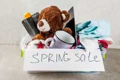 Plastic spring sale box. With toys, clothes gadgets and tools, white grey background copy space royalty free stock image