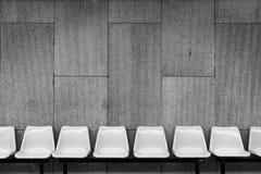 Plastic stoelen op cementmuur Stock Afbeelding