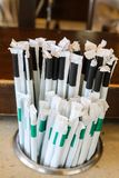 Plastic straws with paper wrappers in counter holder - the straws that many states and countries are outlawing but are still used. Plastic straws with paper Royalty Free Stock Image