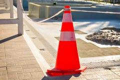 Plastic striped orange cone on the road. Traffic cone.  Stock Photos