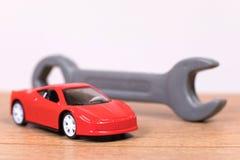 Plastic stuk speelgoed moersleutel naast modelauto stock foto's