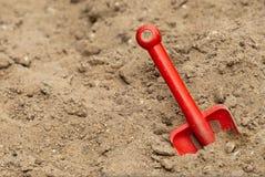 Plastic stuk speelgoed spade in zand Stock Afbeelding