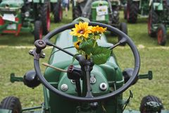 Plastic sunflower on the steering wheel of an old tractor stock photos
