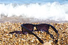 Plastic sunglasses against the background of sea stones. Sea in the background stock photos