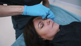 Plastic surgeon checking middle aged woman face before cosmetic surgery.  stock video
