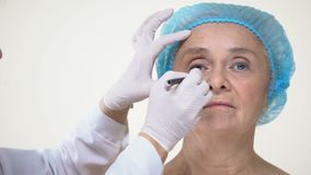 Plastic surgeon preparing old lady for facelift operation, anti-aging therapy stock footage