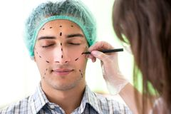 The plastic surgeon preparing for operation on man face. Plastic surgeon preparing for operation on men face Stock Photography