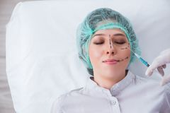 The plastic surgeon preparing for operation on woman face. Plastic surgeon preparing for operation on woman face Stock Photos