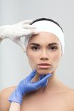 Plastic surgeon touching the beautiful woman face Stock Photos