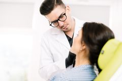 Plastic surgeon using beauty treatments for patients. Young plastic surgeon using beauty treatments for patients Stock Image
