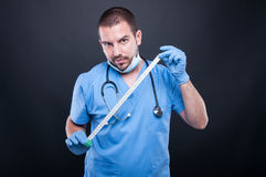 Plastic surgeon wearing scrubs showing measuring tape. On black background Royalty Free Stock Photos