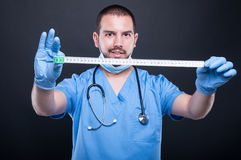 Plastic surgeon wearing scrubs showing measuring tape. And smiling on black background Royalty Free Stock Images