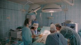 Plastic surgeon wearing surgical clothing performing augmentation mammoplasty stock video