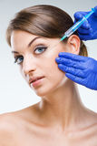 Plastic surgery - Beautiful woman's face with hypodermic needle Stock Images
