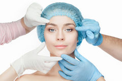Plastic surgery concept. Doctor hands in gloves touching woman face Stock Photos