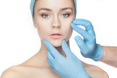 Plastic surgery concept. Doctor hands in gloves touching woman face Stock Image