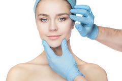 Plastic surgery concept. Doctor hands in gloves touching woman face Stock Photography
