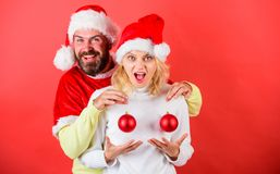 Plastic surgery. Man santa hat hold balls christmas ornament in front of female breasts. Christmas balls symbol implant. Female breasts. Couple excited hold royalty free stock photos