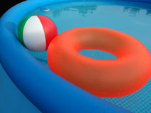 Plastic Swimming Pool. Blue inflatable pool with red floating tire and multicolored beach ball on black background Royalty Free Stock Image