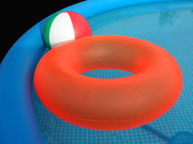 Plastic Swimming Pool. Blue inflatable pool with red floating tire and multicolored beach ball on black background Stock Images