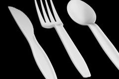 Plastic tableware. A plastic knife fork and spoon on black background Royalty Free Stock Photography