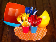 Plastic tableware: bowls, forks, spoons, knives, cups on dark wood. Royalty Free Stock Photo