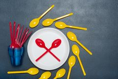Plastic tableware bowls, spoons, and forks on gray background. Set of plastic tableware bowls, spoons, and forks on gray background. Flat lay, top view. Ecology stock photography