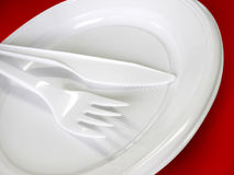 Plastic tableware - knife, fork and plate. Red background royalty free stock photos