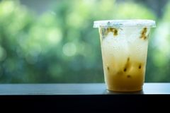 Plastic takeaway cup of iced passion fruit tea. With nature background stock image