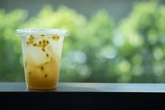Plastic takeaway cup of iced passion fruit tea. With nature background stock photos
