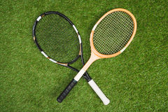 Plastic tennis and wooden badminton rackets on green lawn. Top view of plastic tennis and wooden badminton rackets on green lawn Royalty Free Stock Images