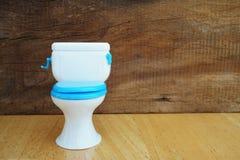 Plastic toilet  toy on grunge wood Stock Image