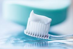 Plastic toothbrush with white toothpaste on a blue table. And green soap background stock photos