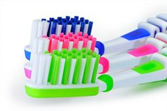 Green, blue and pink toothbrushes are isolated on a white stock photos