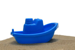 Plastic toy boat on sand isolated. On white Royalty Free Stock Images