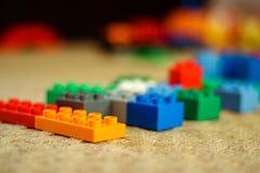 Plastic toy building blocks with defocused background. Plastic toy building blocks sorted in the line with defocused background royalty free stock image