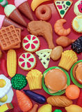 Plastic Toy Food. Collection of several pieces of plastic toy food over red background Stock Photos