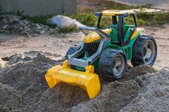 Plastic toy front loader on the sand pile stock photos