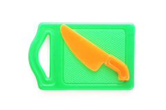Plastic toy green chopping board and orange knife Royalty Free Stock Image