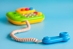 Plastic toy mobile phone on a blue background for children. Stock Photo