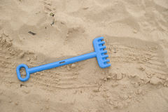 Plastic toy rake on sandy beach Stock Image