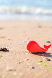 Plastic toy red whale on the seashore for background Stock Images