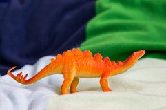 Plastic toy stegosaurus. On white blanket in soft focus Royalty Free Stock Photography
